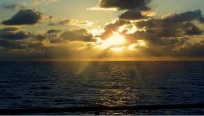 Soleil qui selève derrière des nuages sombres !